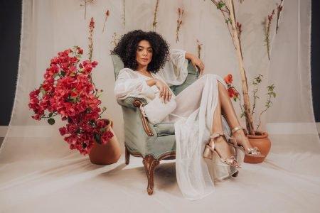 Modelo sentada em poltrona para campanha com flores da Shoestock