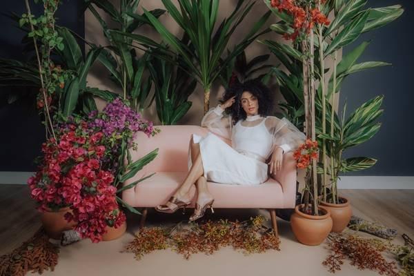 Modelo sentada em sofá para campanha com flores da Shoestock