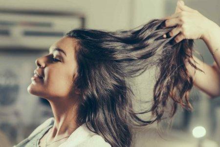 mãos pegam em cabelo de mulher
