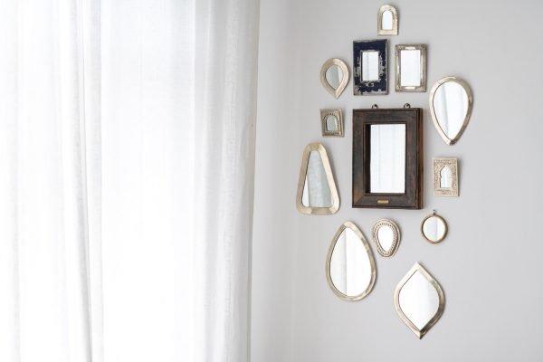 Parede branca com espelhos pequenos