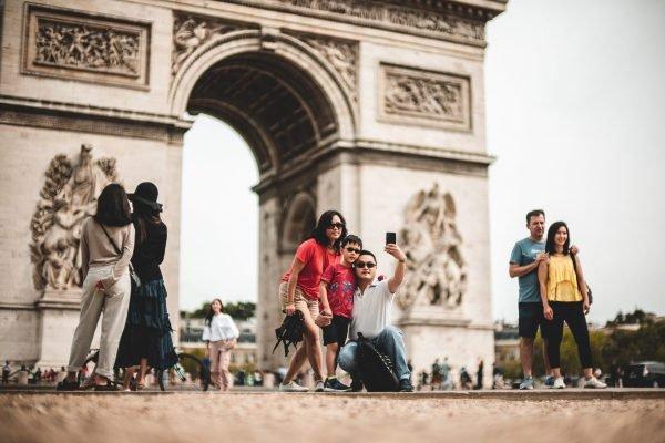 Família tira foto em frente ao Arco do Triunfo, em Paris