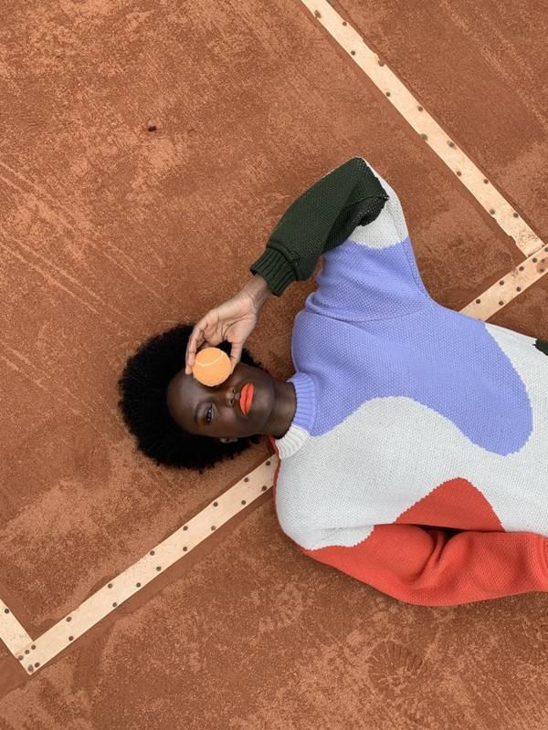 Modelo com tricô colorido da Ginger em quadra de tênis