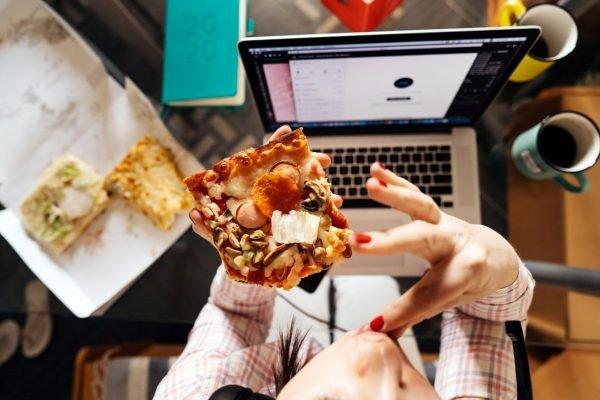 mãos segurando pedaço de pizza e computador a frente