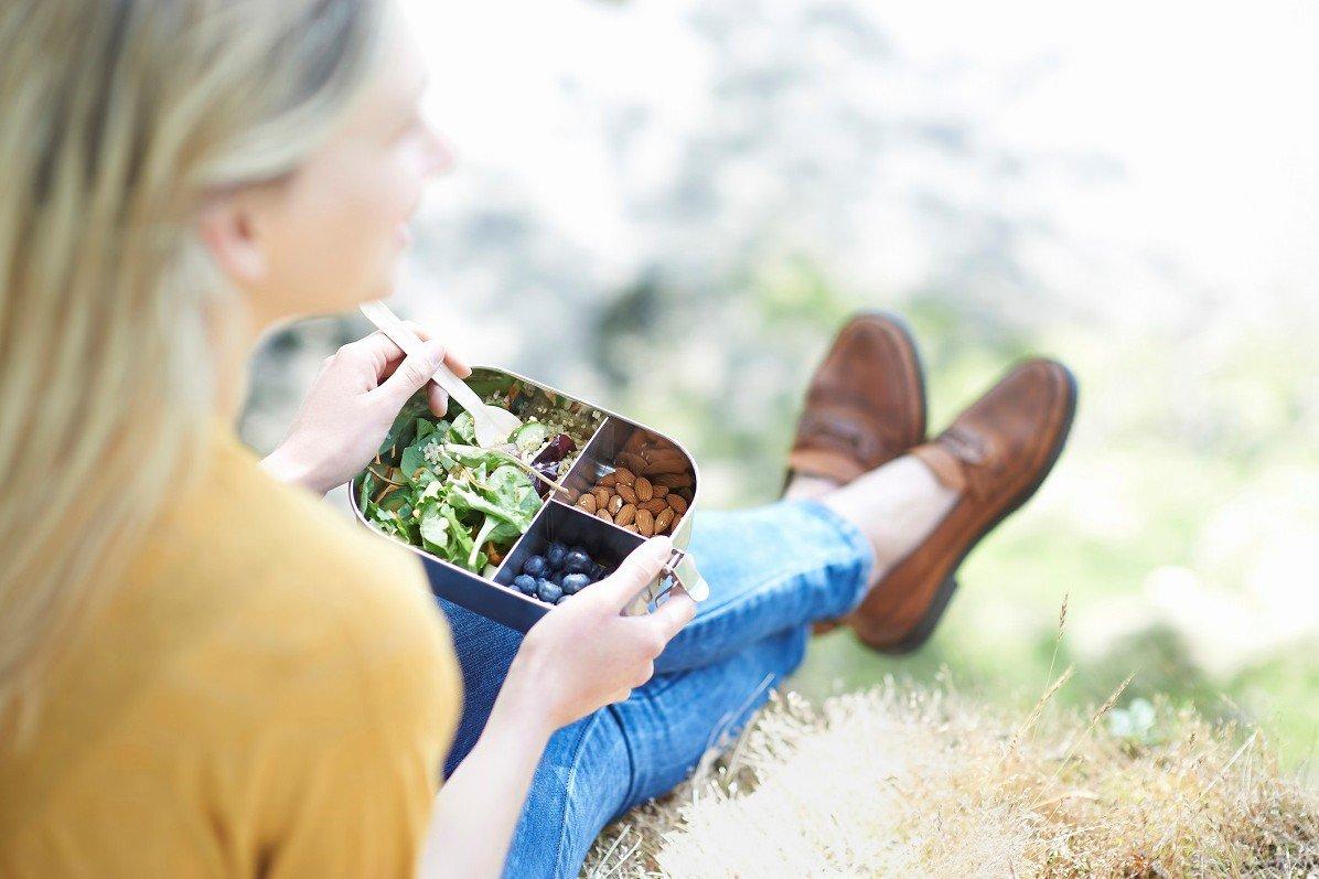 mulher sentada na grama comendo alimentos saudáveis