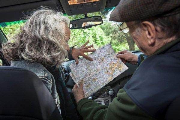 Casal de idosos dirigindo carro