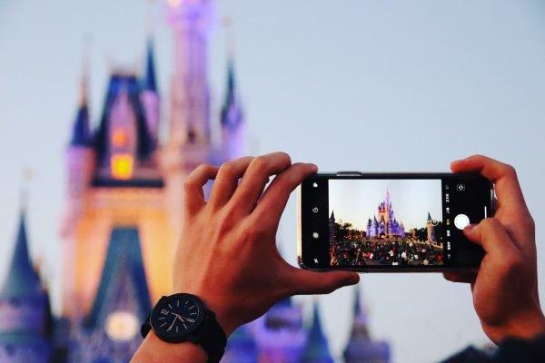 Pessoa tira foto do castelo da Cinderela, na Disney