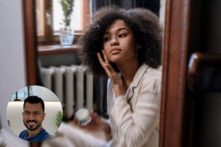 mulher negra passando produto no rosto de frente ao espelho