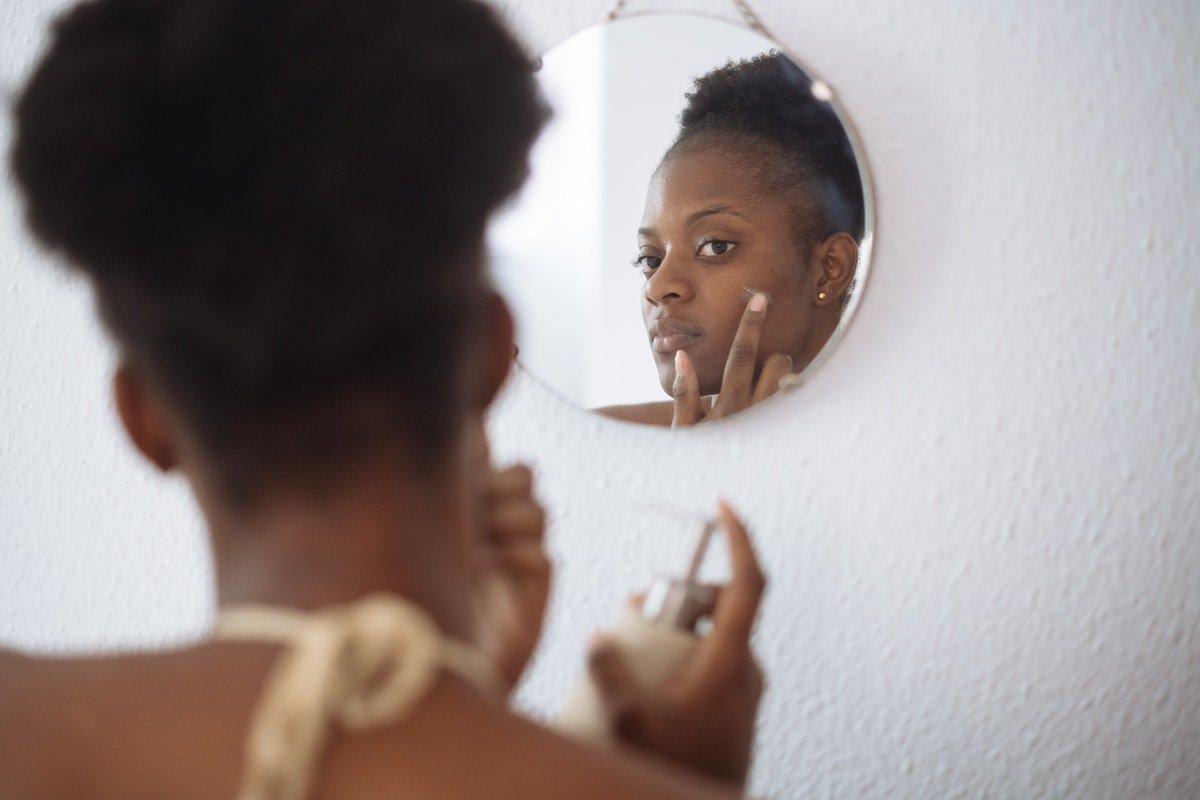 mulher negra aplicando creme no rosto em frente ao espelho