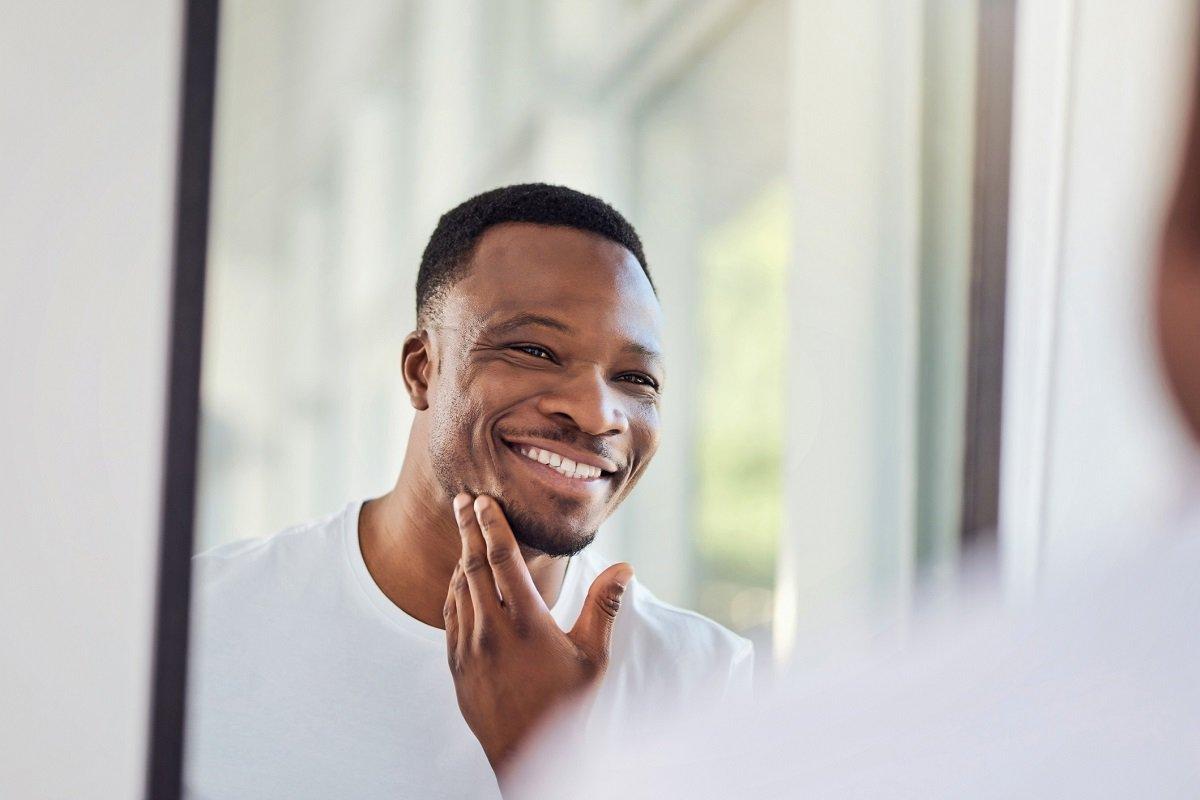 homem negro se olha ao espelho e sorri