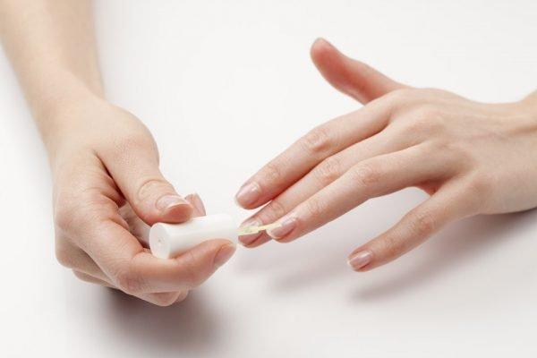 mulher passando esmalte nas unhas
