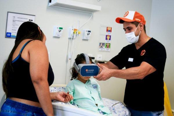 Homem segura óculos de realidade virtual para menina