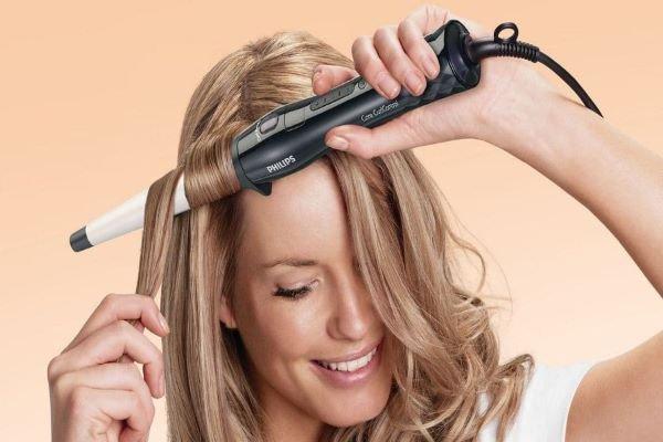Mulher utilizando babyliss no cabelo