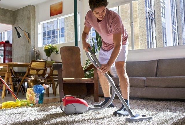 homem aspirando o tapete