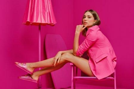 Modelo em campanha da Arezzo com cenário e look rosas