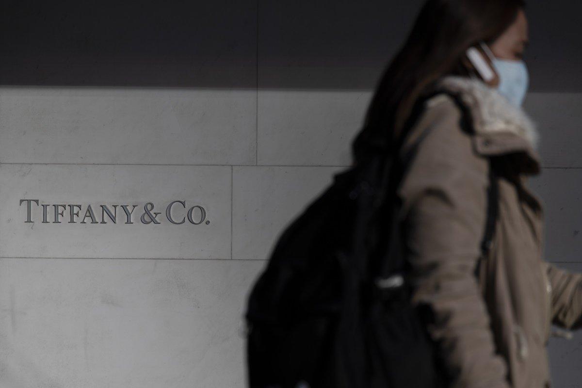 Pedreste de máscara passando por loja da Tiffany & Co., na China