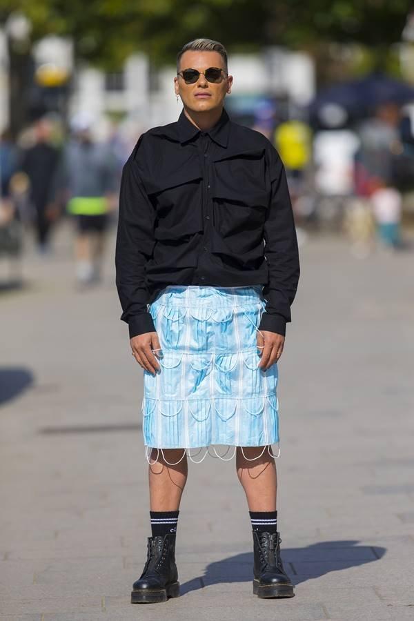 Israel Cassol usando saia feita de máscaras faciais, em Londres
