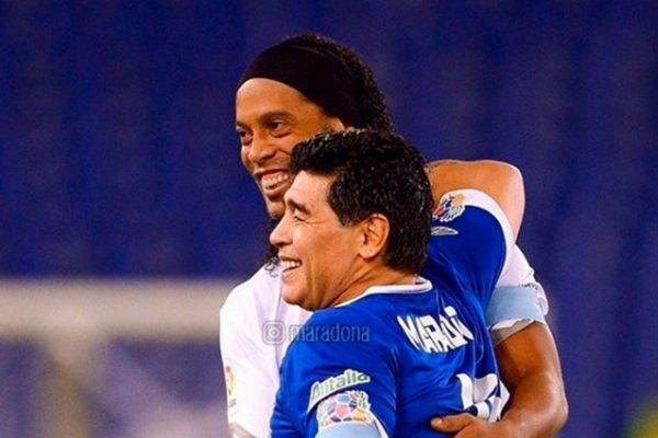 Ronaldinho Gaúcho e Diego Armando Maradona abraçados em jogo festivo