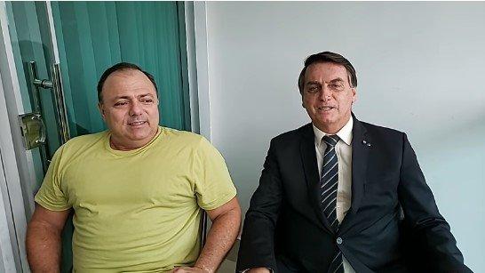 Presidente Jair Bolsonaro sentado ao lado de Eduardo Pazuello, em visita ao ministro da Saúde, com Covid-19
