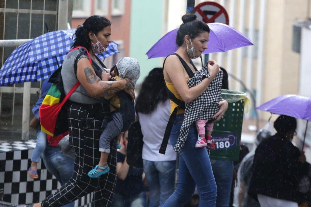 Pessoas aglomeradas se protegem da chuva na região central de São Paulo