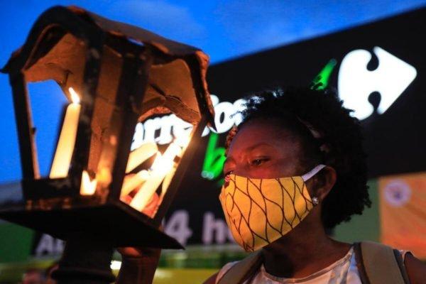 mulher negra com vela em frente ao Carrefour