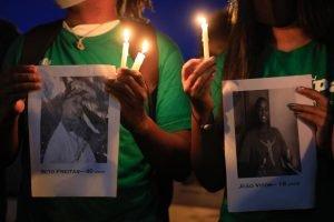 pessoas mostram fotos de homens negros mortos