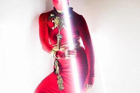 Modelo usa vermelho, com joias, e segura um sabre de luz