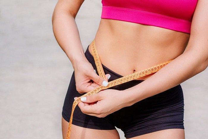 mulher medindo barriga com fita métrica