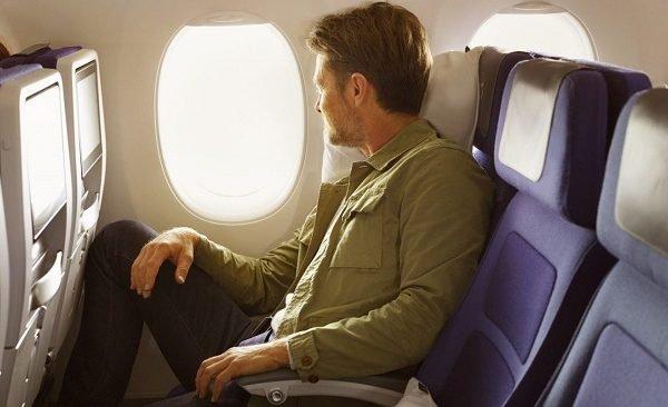 homem sentado em cadeira de avião