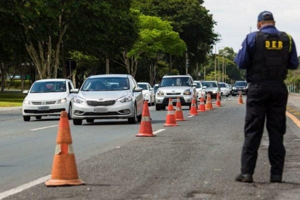 Blitz do DER com agente, cones e carros passando