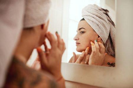 mulher olhando pele no espelho