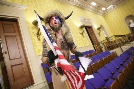 Homem com roupa de chifres segurando bandeira dos EUA