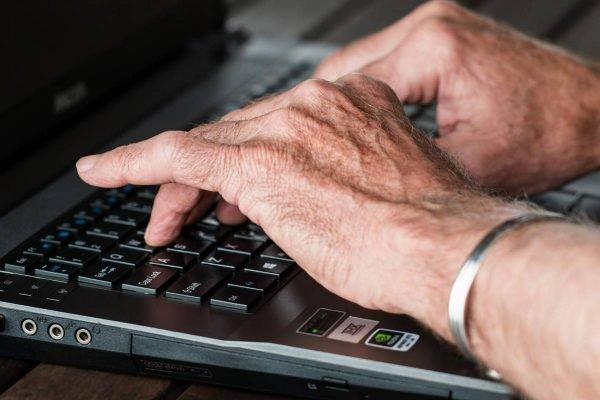 mãos de homem teclando computador