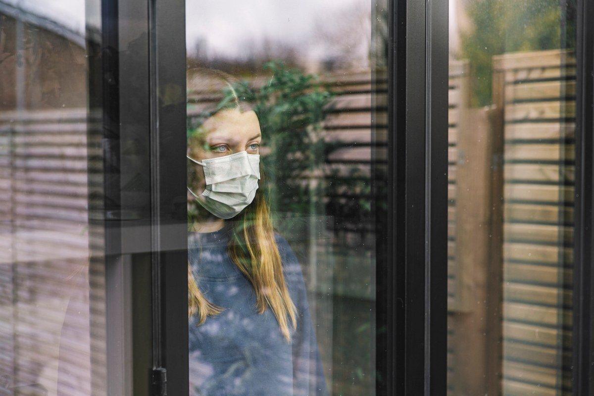 menina de máscara olhando pela janela
