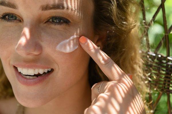 Mulher aplica protetor solar no rosto
