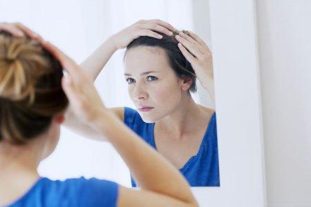 Mulher olha o cabelo no espelho