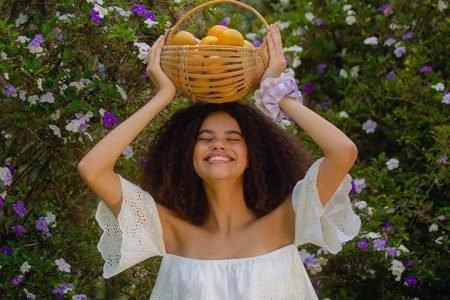 Modelo com cesta de frutas na cabeça, em campanha da Renner