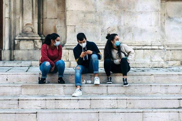 adolescentes de máscara sentados em uma escada