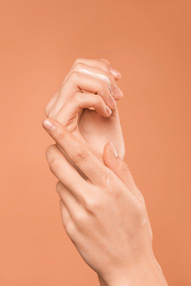 mãos de pessoa em fundo laranja