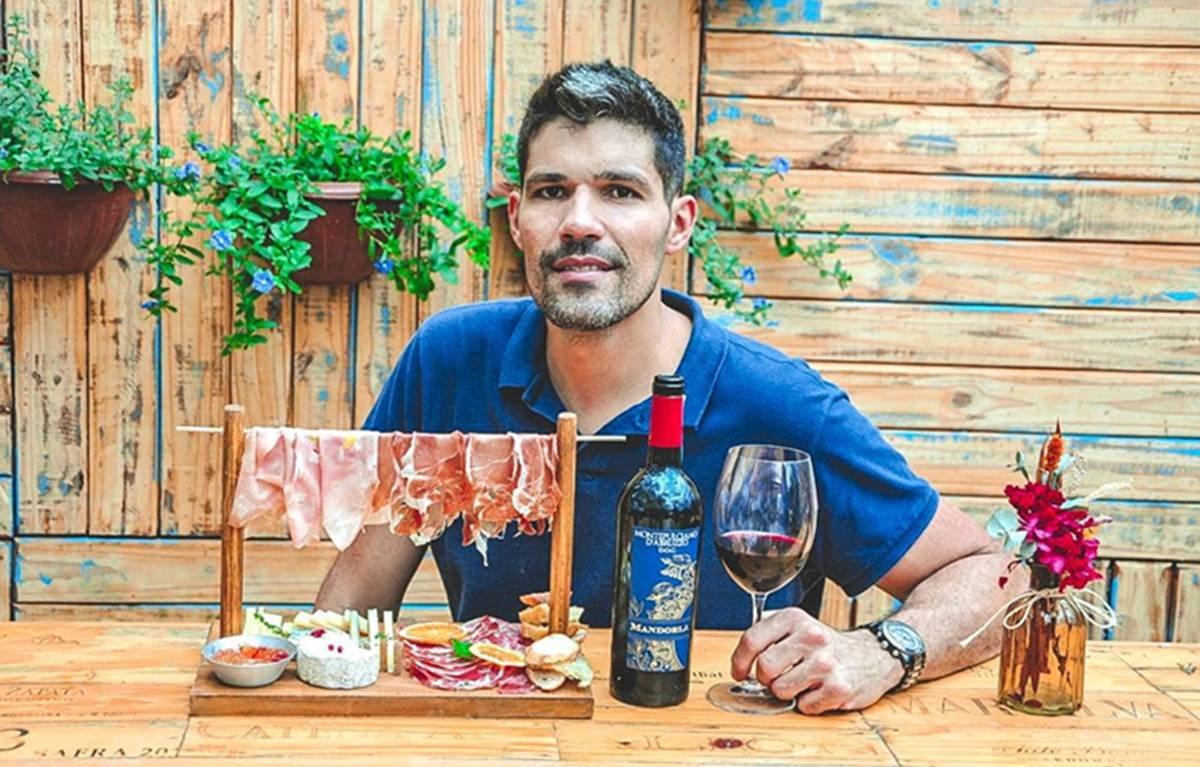 Homem segurando uma taça de vinho que está sobre uma mesa de madeira junto com uma garrafa de vinho e uma tábua de frios