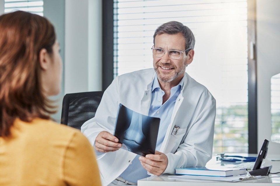 paciente conversa com médico ortopedista que segura exame de raio x