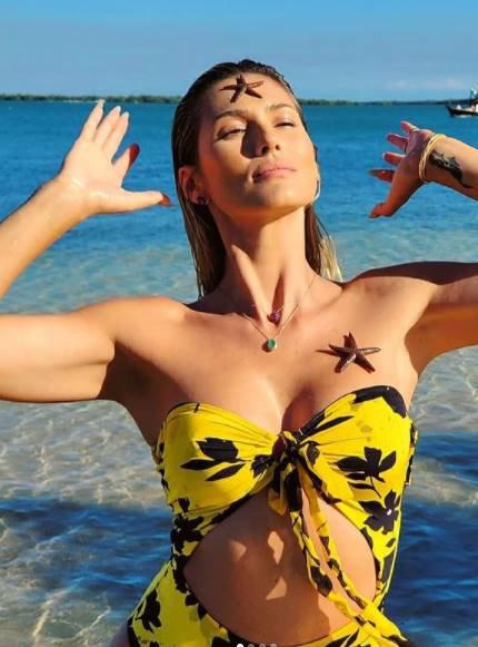Lívia Andrade na praia com sereias no corpo