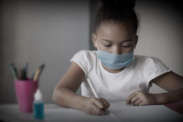 Criança com máscara escreve em caderno