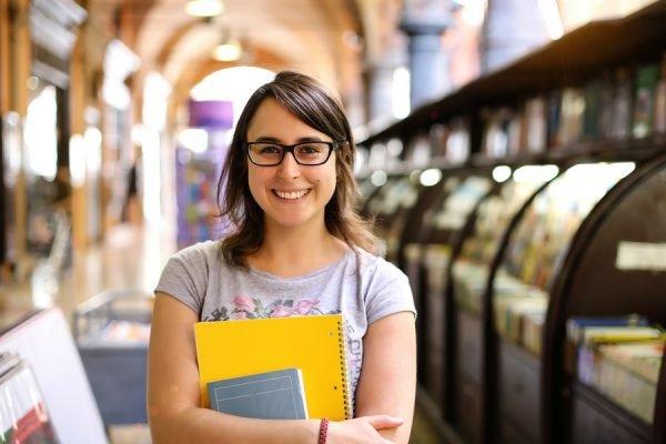 mulher de óculos de grau segurança cadernos