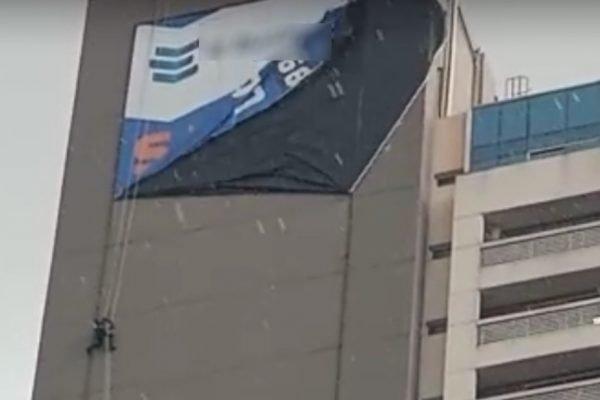 Alpinista industrial fica presa em prédio durante forte temporal