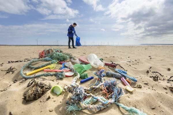 Homem em praia poluída