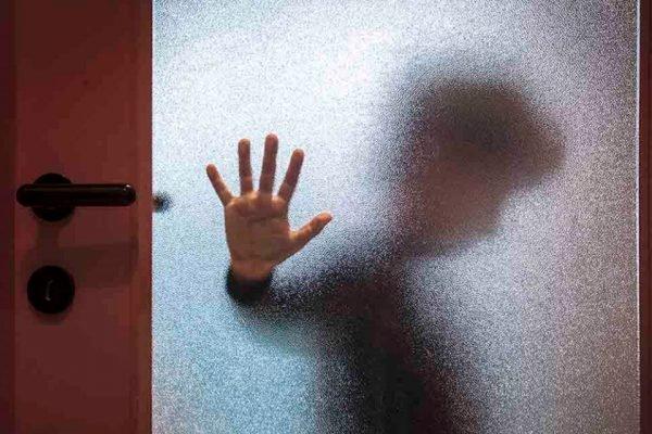 garoto com a mão no vidro