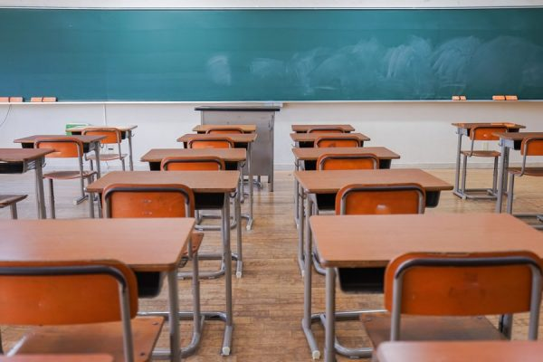 carteiras infileiradas em uma sala de aula vazia