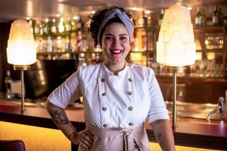 Mulher vestida de dolmã de chef sorrindo