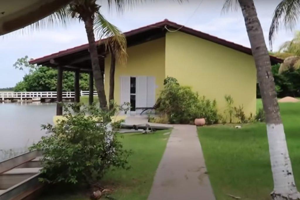 ao fundo, casa amarela e com acesso de concreto que direciona os visitantes até o local. é um dos quartos da fazenda talismã, do cantor leonardo
