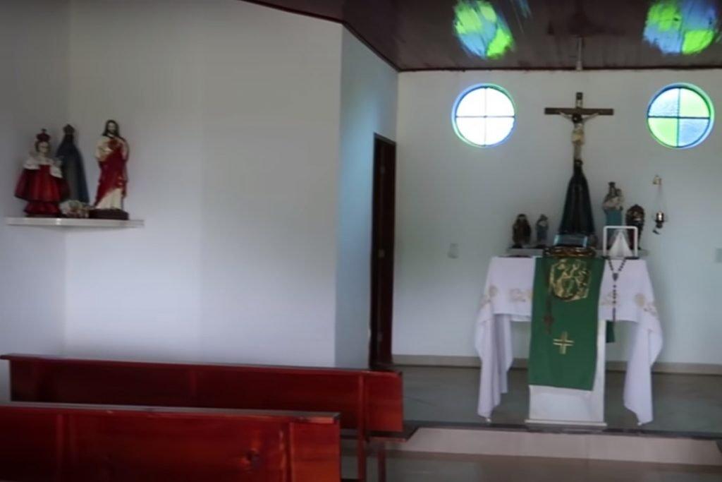 interior da capela da fazenda talismã do cantor leonardo. ao fundo, imagem de jesus na cruz e alguns bancos